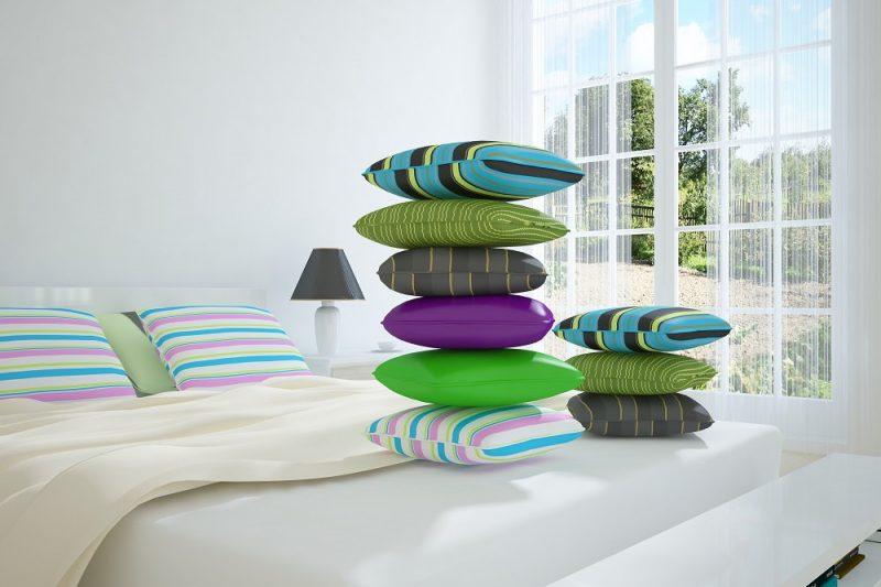 Camera da letto luminosa in primavera con tanti cuscini colorati
