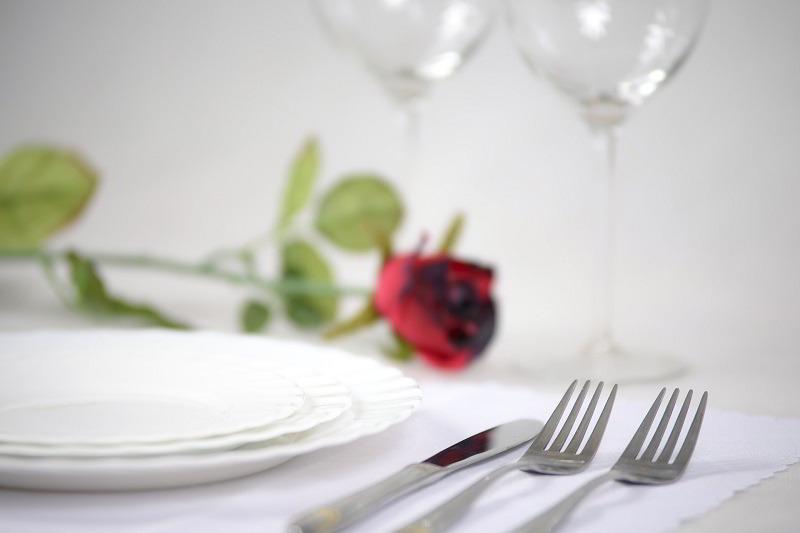 Tavola apparecchiata in modo elegante e romantico con segnaposto un bocciolo di rosa
